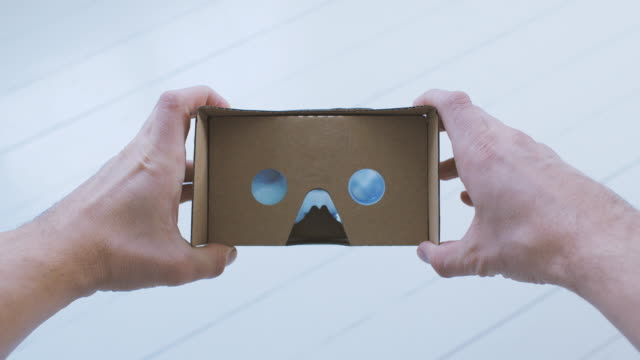 man using cardboard virtual reality glasses pov - optical instrument stock videos & royalty-free footage