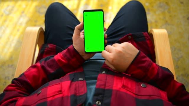 クロマキーグリーンスクリーンスマートフォンを使用している男 - 空白の画面点の映像素材/bロール