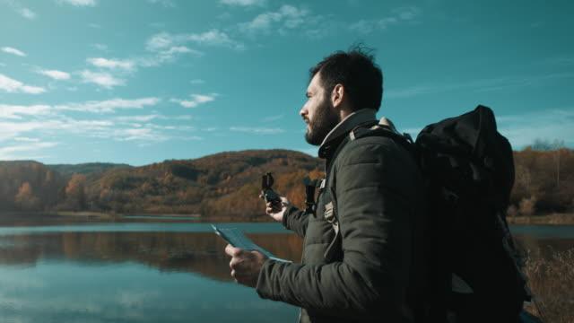 mann mit kompass und karte durch die see - kompass stock-videos und b-roll-filmmaterial