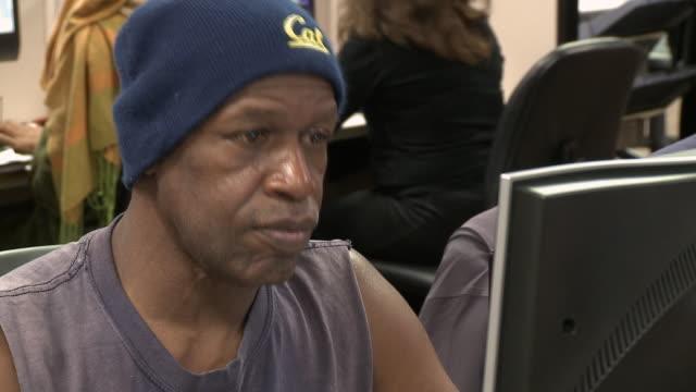 man using computer in job center/ antioch, california, usa/ audio - ノースリーブトップ点の映像素材/bロール