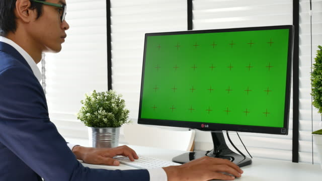 Man Using computer monitor with green screen