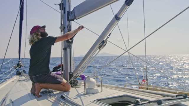 mann mit kurbel, anpassung der takelage auf sonnigen segelboot, real-time - besatzung stock-videos und b-roll-filmmaterial