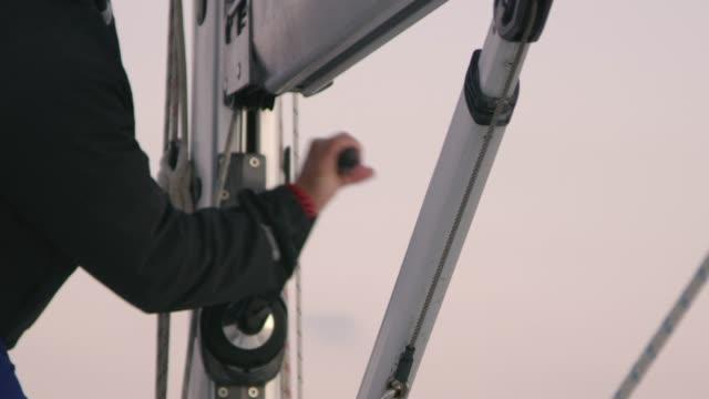 4k mann mit kurbel takelage auf segelboot, zeitlupe einstellen - besatzung stock-videos und b-roll-filmmaterial