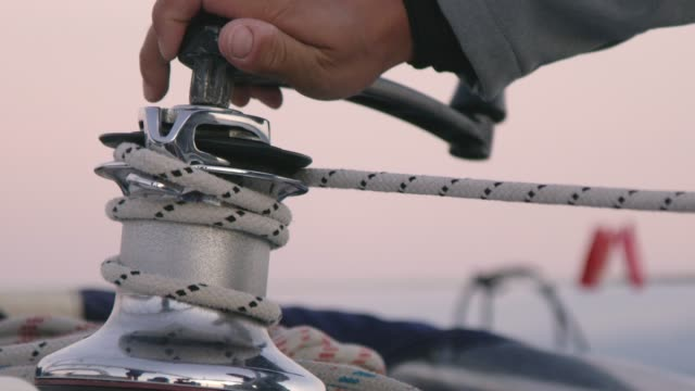 4k man using crank to adjust rigging on sailboat, slow motion - rigging nautical stock videos & royalty-free footage