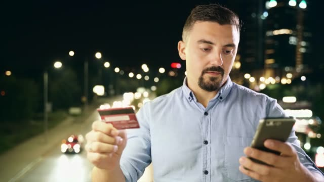 Man using credit card and smart phone online shopping outdoors at night