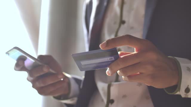 vídeos de stock, filmes e b-roll de homem que usa o cartão de crédito em linha - pagamento móvel