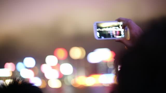 MS PAN SELECTIVE FOCUS Man using digital camera to photograph city at night / Hong Kong Harbor, China