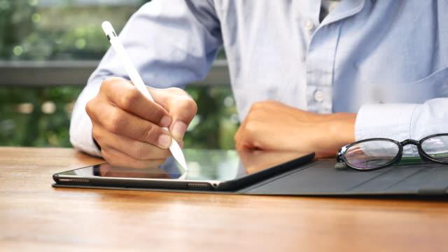 man använder digital penna skriva på tablet pc - sladdlös telefon bildbanksvideor och videomaterial från bakom kulisserna