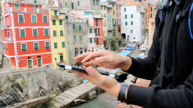 vídeos y material grabado en eventos de stock de hombre usando tableta digital en el fondo de aldea de pescadores de riomaggiore. - cinco objetos