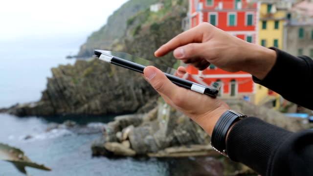 man använder digital tablett på riomaggiore fisherman village bakgrund. - fem objekt bildbanksvideor och videomaterial från bakom kulisserna