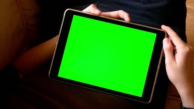 Mann mit digitalen Tablet-Computer mit Greenscreen für Chroma-Key mit mehreren Bildschirm-Touch-Gesten und lag auf sofa