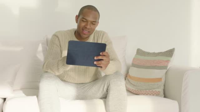 vídeos de stock, filmes e b-roll de man using digital tablet device - almofada