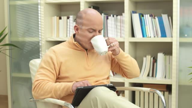 HD DOLLY: Man Using Digital Tablet During Coffee Break