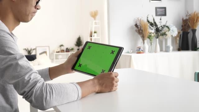家庭でデジタルタブレットグリーンスクリーンを使用している人 - 代理点の映像素材/bロール