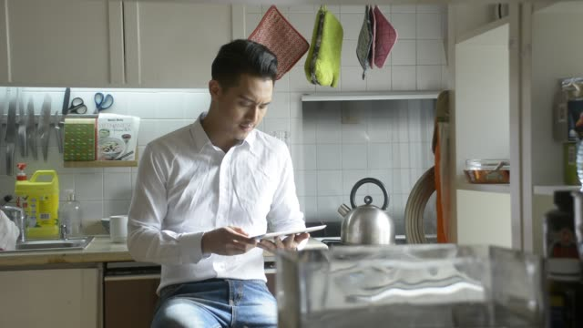 man using digital tablet in kitchen - oven mitt stock videos and b-roll footage