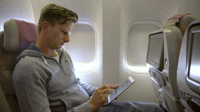 ms man using digital tablet on the airplane - passenger cabin stock videos & royalty-free footage