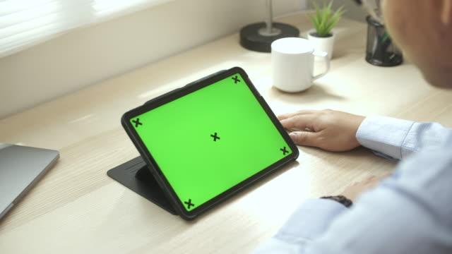 vídeos de stock, filmes e b-roll de homem usando tablet digital com tela verde em casa - modelo web