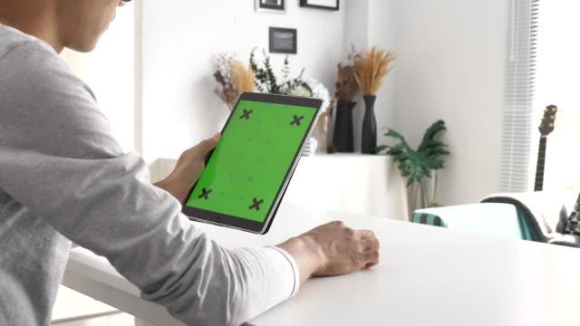 mann mit digital tablet mit greenscreen zu hause - über die schulter stock-videos und b-roll-filmmaterial