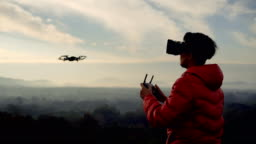 Man using drone with VR headset in the morning on mountain view