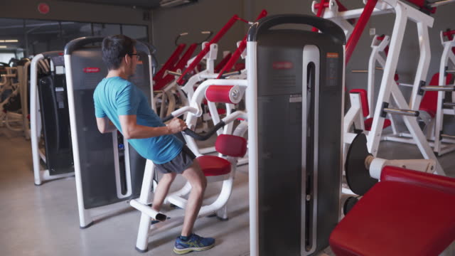man using exercise machine the wrong way at the gym. funny comedy concept - sweat stock videos & royalty-free footage