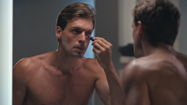 vídeos de stock e filmes b-roll de man using eye roll on - desodorante