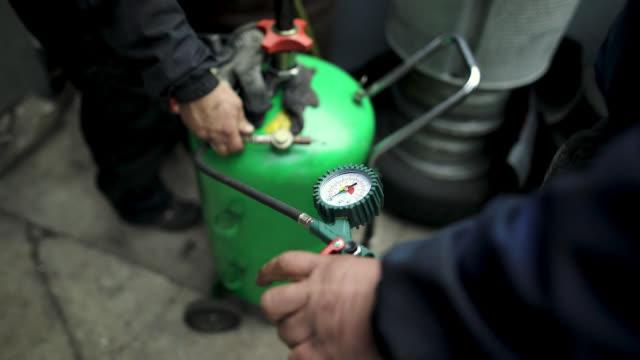 ガレージの背後にガスコンプレッサーを使用して男 - 空気弁点の映像素材/bロール