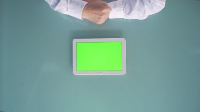 vídeos y material grabado en eventos de stock de man using green screen tablet top view - table top view
