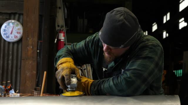 MS Man using grinder during project in metal workshop