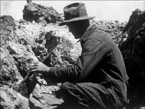 B/W 1927 PROFILE man using hammer + chisel on rock looking for gold / Nevada / SLATE at end