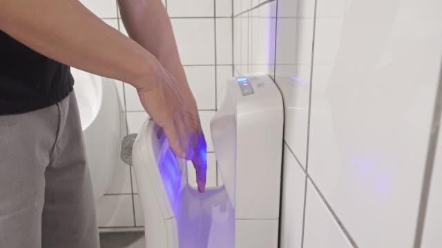 man using hand drier - asciugamano video stock e b–roll