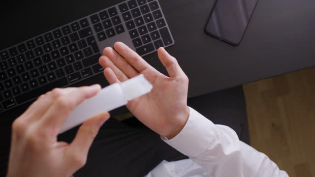 man using hand sanitiser at work - disinfection stock videos & royalty-free footage