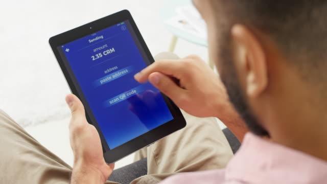 mann mit seiner digital-tablette kryptowährung senden - über die schulter stock-videos und b-roll-filmmaterial