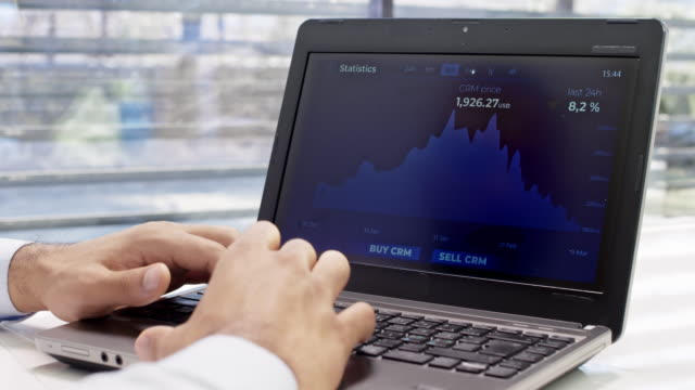 man using his laptop in the office to check the value of cryptocurrency - cryptocurrency stock videos & royalty-free footage