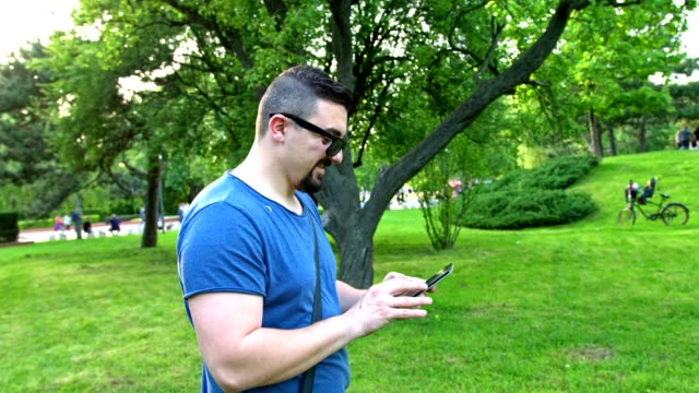 Man using his smart phone while walking in the park