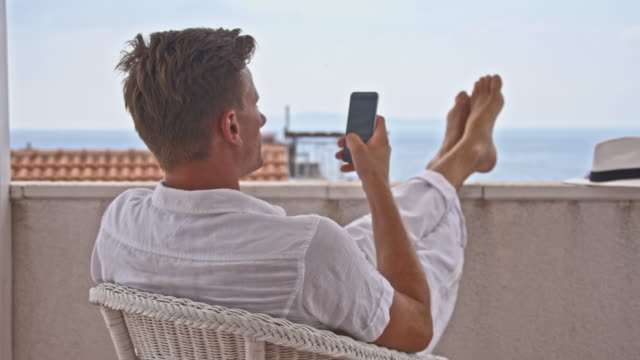 DS Man using his smartphone in a seaside hotel