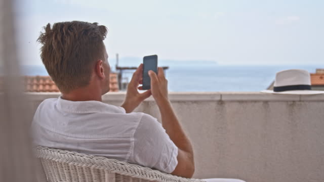 DS Man using his smartphone on the balcony