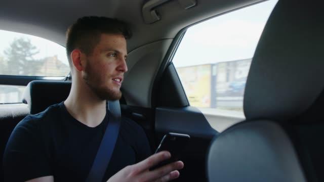 vídeos de stock e filmes b-roll de man using his smartphone while driving in back of a car - atrás