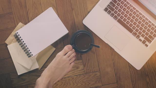 Man met Laptop en koffie met voeten