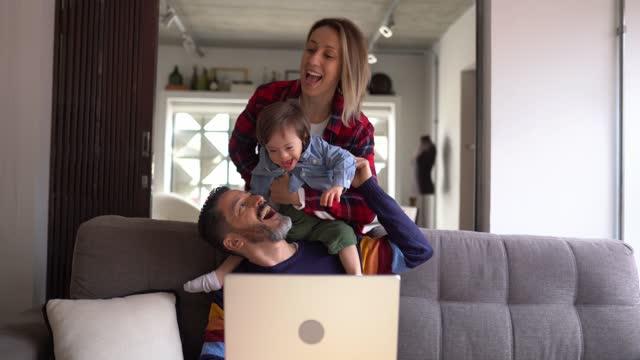 vídeos de stock, filmes e b-roll de homem usando laptop e esposa e filho com necessidades especiais chegando em casa - começo