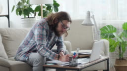 Man using laptop and writing notes