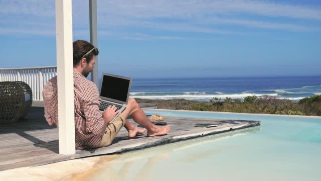 man using laptop by pool - プレイドシャツ点の映像素材/bロール