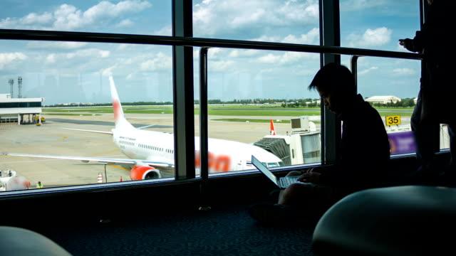 hd: uomo utilizzando un computer portatile in aeroporto terminal - solo un uomo di età media video stock e b–roll