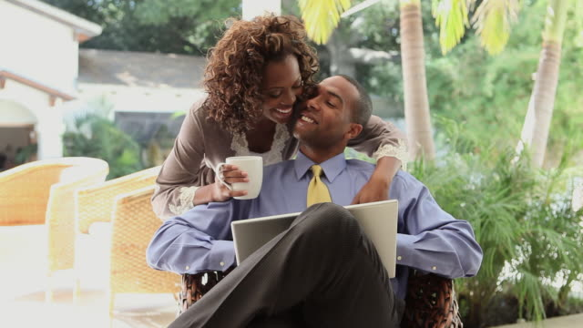 vídeos de stock e filmes b-roll de man using laptop, girlfriend in dressing gown comes to kiss him - camisa e gravata
