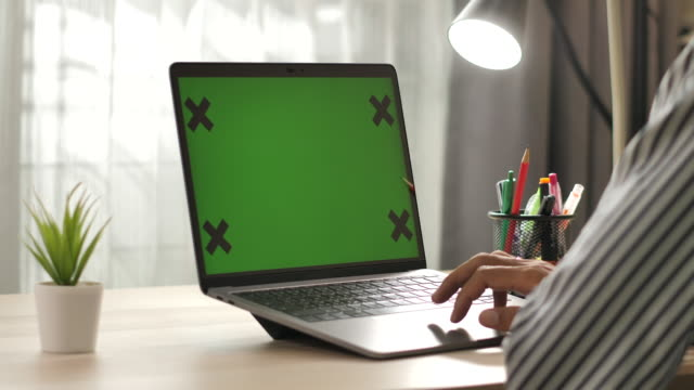 vídeos de stock e filmes b-roll de man using laptop green screen on desk at home - computer