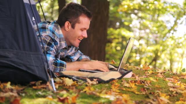 Man using laptop in camping tent
