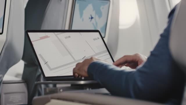 vidéos et rushes de homme utilisant l'ordinateur portatif dans le jet d'affaires - voyage d'affaires