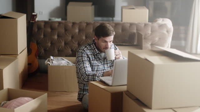 Man using laptop in his new home