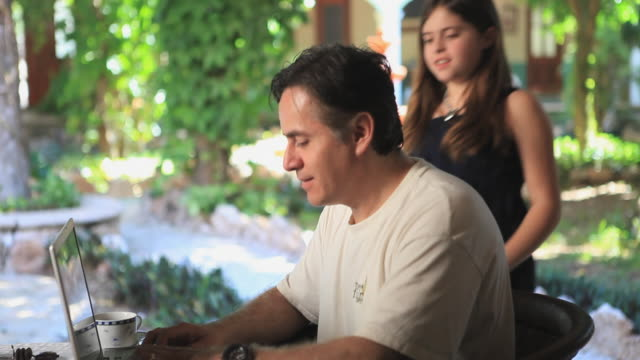 MS Man using laptop in patio, daughter joining, Valladolid, Yucatan, Mexico