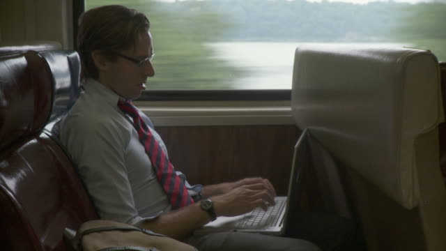 ms man using laptop in train / new york city, new york, usa - använda en laptop bildbanksvideor och videomaterial från bakom kulisserna