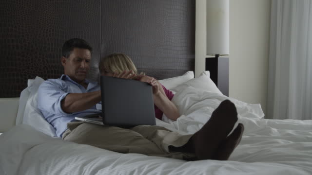 WS Man using laptop on bed, disappointed woman lying next to him / South Beach, Miami, Florida, USA